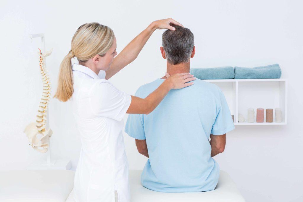 Doctor adjusting neck of car accident victim